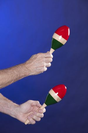 vertical format: A set of two maracas being played isolated against a blue background in the vertical format. Stock Photo