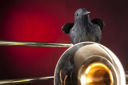 horizontal format horizontal: A Halloween trombone and blackbird crow isolated against a red spotlight background in the horizontal format.