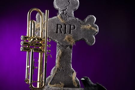 A Halloween trumpet with a gravestone and blackbird crow against a purple spotlight background. photo