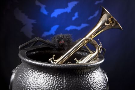A gold brass Halloween trumpet in a witch pot and bats against a dark blue background. Banco de Imagens