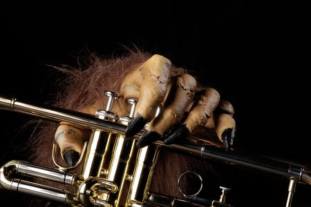 A gold brass Halloween trumpet with a monster hand against a black background.