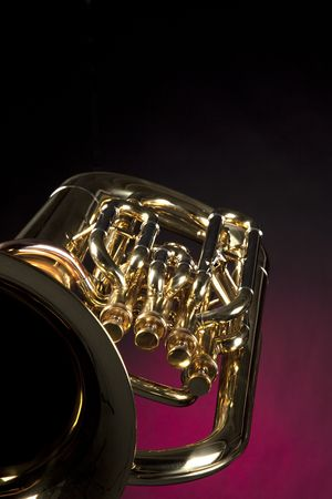 tuba: A gold brass euphonium tuba baritone isolated against a dark red background.