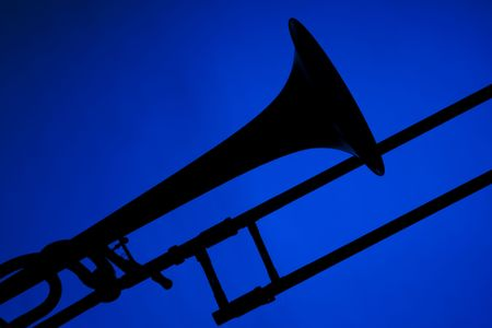 青い背景に対して隔離されるトロンボーン音楽・楽器シルエット。