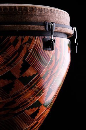 An orange African or Latin Djembe conga drum isolated on black background in the vertical for Stock Photo