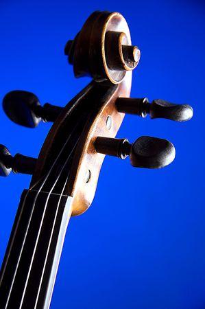 垂直方向の形式で青い背景に分離されたバイオリンのスクロール。 写真素材