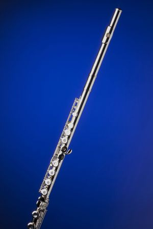 A silver flute isolated against a spotlight blue background in the vertical format. Stock Photo - 5874444