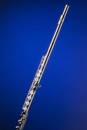 Een Zilveren fluit geïsoleerd tegen een spotlight blauwe achtergrond in de verticale indeling.