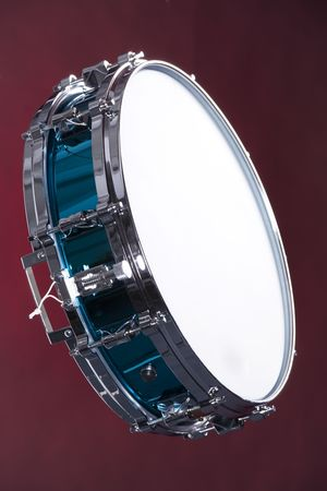 vertical format: A blue finish snare drum isolated against a dark red background in the vertical format.