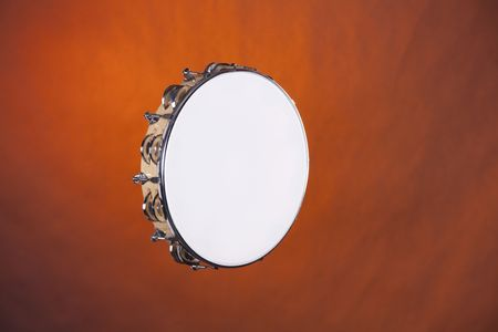 horizontal format horizontal: A wood tambourine isolated against spotlight gold background in the horizontal format.