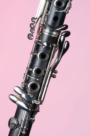 vertical format: A clarinet musical instrument isolated against a light pink background in the vertical format.