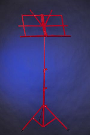 A red folding music stand isolated against a spotlight blue background in the vertical format.