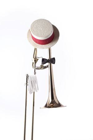 A trombone dressed in bow tie, gloves, and Dixieland hat isolated against a white background in the vertical format.