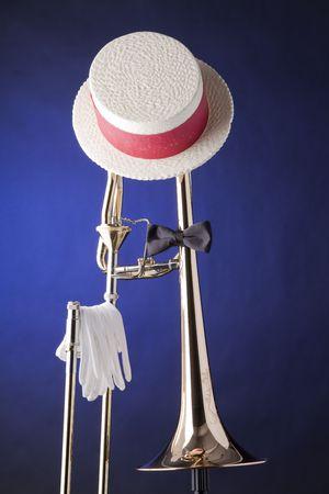 trombon: Un tromb�n profesional con guantes, aislados contra un fondo de foco azul, corbata y sombrero. Foto de archivo