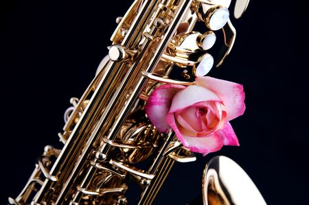 horizontal format horizontal: A pink rose mounted on a gold brass saxophone isolated against a black background in the horizontal format.