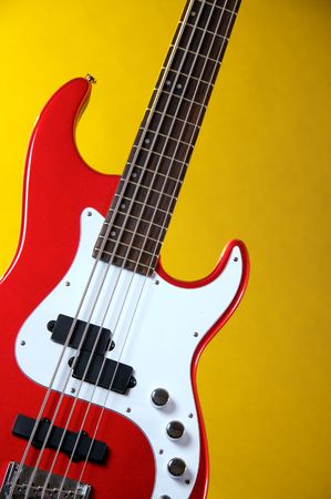 vertical format: A metallic red electric guitar isolated against a yellow background in the vertical format.