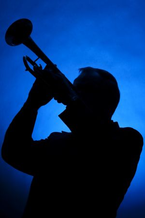 A silhouette of a trumpet player isolated against a blue spotlight in the vertical format.