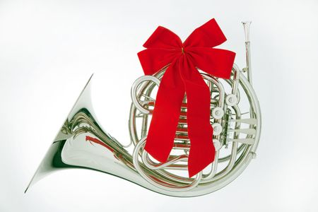 A silver French horn with a red ribbon bow isolated against white background in the horizontal format.