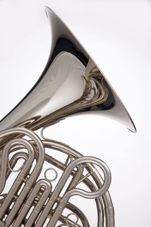A professional silver French horn isolated against a white background in the vertical format.