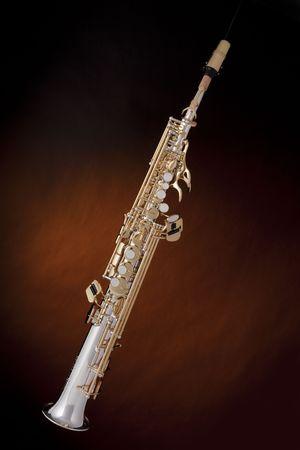 soprano saxophone: Un oro y plateado profesional saxof�n soprano aislado contra un fondo de oro de foco. Foto de archivo
