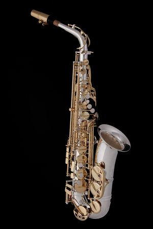 A complete professional silver and gold alt saxophone isolated on a black background. photo