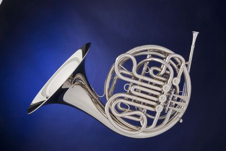 french horn: A professional silver French horn isolated against a spotlight blue background.