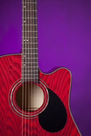 A red wood acoustic electric guitar isolated against a spotlight purple background. Stock Photo