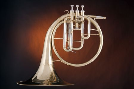 A gold antique peck-horn or French horn isolated against a spotlight gold background. photo