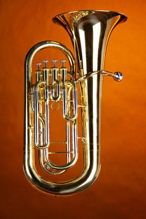 A complete gold brass tuba euphonium isolated against a spotlight gold background.