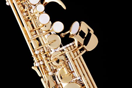 A professional gold soprano sax up close isolated against a black background.  photo