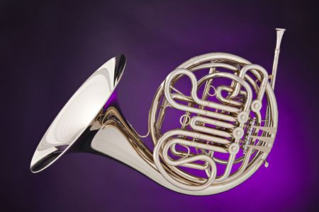 french horn: A silver French horn isolated against a spotlight purple background.