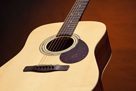 An acoustic guitar with a natural wood finish isolated on a spotlight gold background. photo