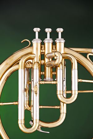 An antique French horn or peckhorn isolated against a spotlight green background.