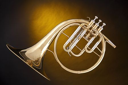 An antique French horn or peckhorn isolated against a spotlight yellow background with copy space. photo