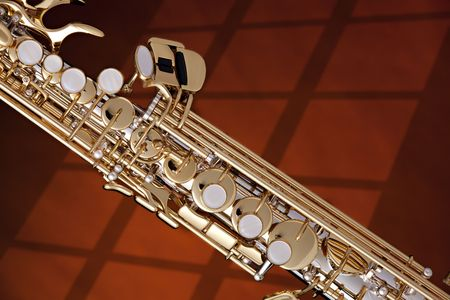 A professional silver and gold soprano saxophone isolated on a window shadow. photo