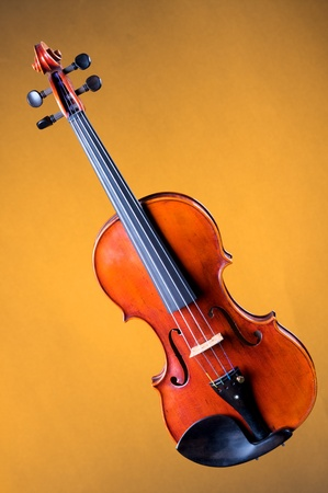 A complete violin viola isolated against a gold background in the vertical format with copy space. Stock Photo