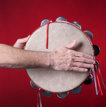 played: A tambourine being played isolated against a red background in the square format with copy space.