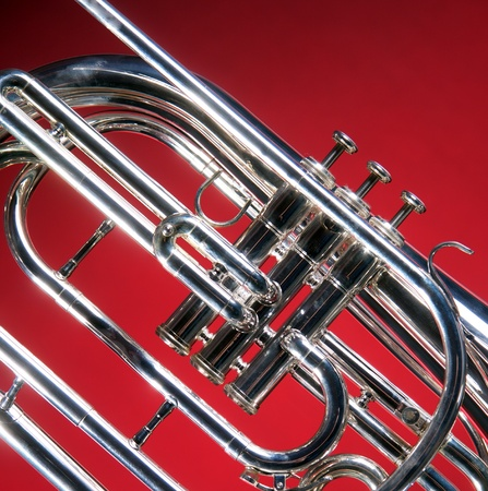 A marching French horn up close isolated against a red  back ground in the square format with copy space. Stok Fotoğraf