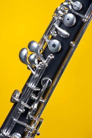 An oboe up close isolated against a yellow gold background in the vertical format with copy space.