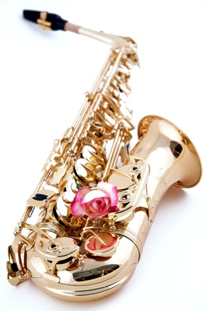 A gold saxophone with a pink rose isolated on a high key white background in the vertical view. photo
