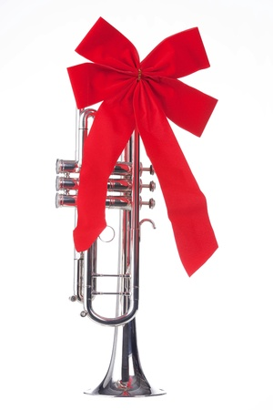 A Christmas silver trumpet with a red bow isolated against a white background.
