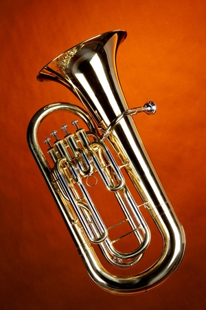vertical format: A gold Euphonium tuba baritone horn isolated against an orange background in the vertical format. Stock Photo
