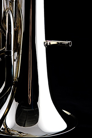 tuba: A brass gold bass tuba euphonium isolated against a black background in the vertical format with copy space.