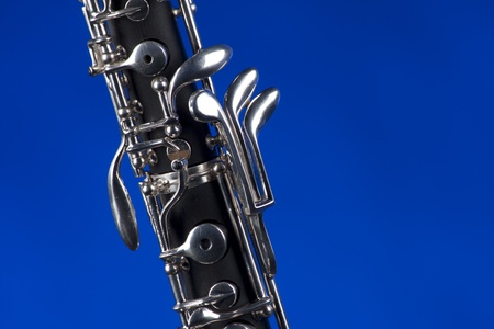 double reed: An oboe up close isolated against a blue background in the horizontal format with copy space.