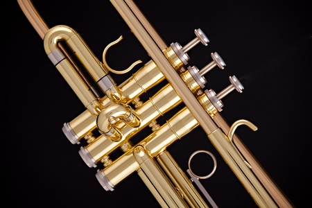 horizontal format horizontal: A professional gold trumpet isolated against a black background in the horizontal format.