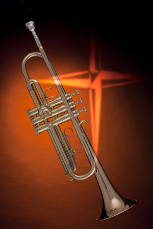vertical format: A gold trumpet or cornet with a cross against an orange background in the vertical format. Stock Photo