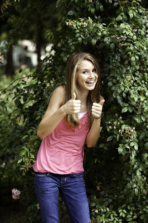 A pretty cute teenage female girl standing against  green vines outside