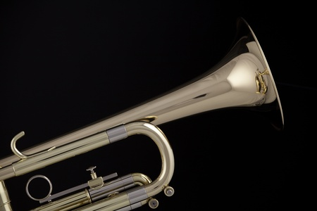 brass instrument: A gold and brass trumpet or cornet isolated against a black background.