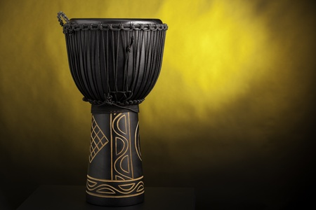A black djembe conga drum isolated against a yellow spotlight background. photo