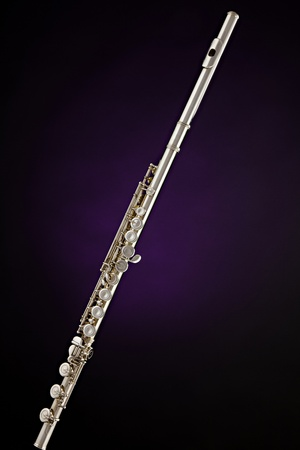 A professional silver flute music instrument isolated against a spotlight purple background. Stock Photo