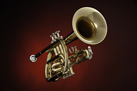 A gold brass cornet or trumpet isolated against a spotlight red background
